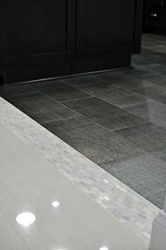 Floor tile transition incorporates a band corresponding with backsplash