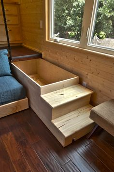 Tiny house on wheels with a slid out bed that stores under the kitchen. Designed and built by Tiny Home Builders.