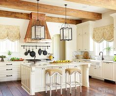 Equipped with rustic beams and wide wood floor planks, this kitchen takes a graceful turn. Painted cabinetry, carved island corbels and pilasters, marble countertops, and chic window shades add a stately air to the work space.
