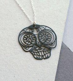 """Mexican Skull halskæde – Sort/sølv  Symbolsk og detaljeret sort vedhæng inspireret af de mexicansk """"Day of the Dead"""" dødningehoveder - supersmart og samtidig en hilsen til de savnede. Materialet er sort pulverlakeret messing med mat sort finish. Kæden er i sterling sølv."""