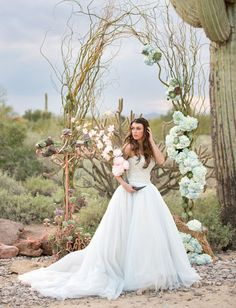 Curly willow and fluffy floral desert wedding arch dotted with succulents. Photo: Amy and Jordan Photography Design: Encore Creative for Allure Bridals