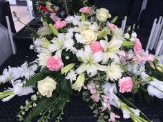 White gladiolus, oriental lilies, roses & light pink carnations & dendrobium orchids casketspray by Cyndy Smith