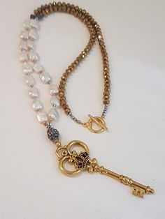 Long necklace of cultivated pearls, gilded crystals and LlaveDorada pendant. Key, Pearls Necklace. Boho Style. Materials: Cultured pearls, Tibetan beaded crystals. Colors: white, gold, silver. Dimensions: 25-inch Collar length. Shipments: Worldwide Shipping to all over the world
