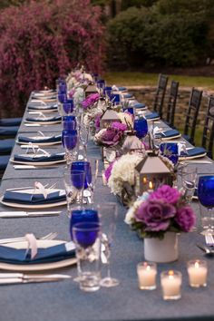 The tablescapes featured navy blue denim tablecloths, hammered highball classes, and cobalt blue goblets. They were topped with shimmering votives, hurricane lanterns, and arrangements of hydrangea, dahlias, thistle, lavender, and dusty miller. | Photo by Jayd Gardina Photography