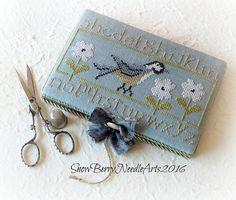 A beautiful cross stitched needle book to decoratively hold sewing and needlework supplies.