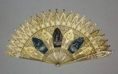 Brisé fan of horn in the Gothic Revival style, with ends shaped to resemble crocketed pinnacles, the whole painted in gilt with cut steel piqué work. The middle section is decorated with 7 Gothic arches, 3 of them painted in grisaille. French c1820. Fitzwilliam Museum.