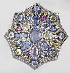A multi-colored sapphire, diamond and blackened eighteen karat gold brooch-pendant  the openwork single-cut diamond plaque with octagonal, scalloped outline, set with oval, pear and circular-shaped light blue, yellow, and purple sapphires; estimated total diamond weight: 2.60 carats; estimated total sapphire weight: 51.50 carats.