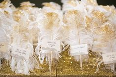 Gold glitter feather escort cards: http://www.stylemepretty.com/oklahoma-weddings/oklahoma-city/2015/09/10/glamorous-spring-oklahoma-city-wedding/ | Photography: Randy Coleman - http://www.randycolemanphotography.com/