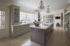 Mark Wilkinson English Classic - A stunning kitchen complete with it's own contemporary sculpture in this amazing neo-classic. The pale lilac and soft grey tones of the hand-painted units with white marble worktops have a calming effect which combine to give the room a real personality.