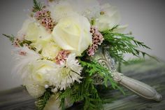 Winter bouquet, White roses, cedar, pink wax flower, snowflake mums, snowball mums.  Silver wedding holder  Crystal Springs Florist Benton Harbor Michigan
