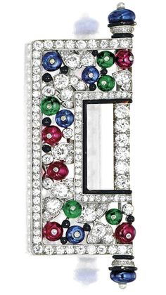 ART DECO GEM-SET, ENAMEL AND DIAMOND BROOCH, CIRCA 1920. The symmetrical plaque composed of ruby, emerald and sapphire beads, decorated throughout by old-cut diamonds and enhanced by a black enamel rim, flanked on each side with a seed pearl, the diamonds and coloured gemstones together weighing approximately 5.00 and 6.80 carats respectively, mounted in platinum. #ArtDeco #brooch