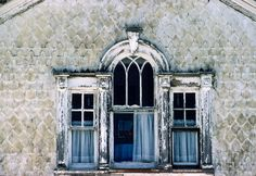 Old windows and walls in disrepair of old victorian house; Old Colorado City, Colorado
