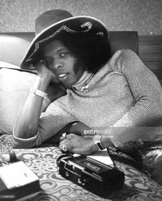 Sly Stone of the psychedelic soul group 'Sly And The Family Stone' poses for a portrait laying on a bed with a fancy hat in 1973.