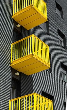 Building detail with yellow balcony on grey/black facade by Marko | Stocksy United
