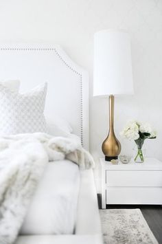 Love the look of this traditional all-white bedroom with a studded fabric headboard, faux fur throw blanket, and white modern nightstand paired with the dramatic, sculptural brass lamp.