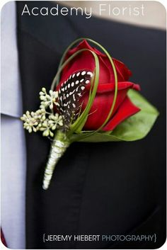 A black and white spotted feather adds a little pizzazz to a classic red rose boutonniere