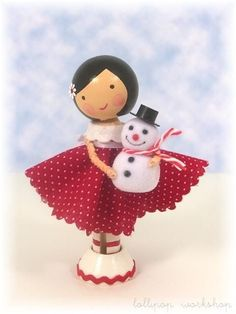 Clothespin Doll:  Girl wearing red with white polka dot dress holding a mini snowman
