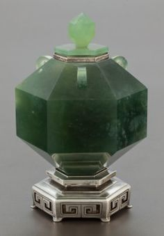 A JAPANESE JADE AND SILVER MOUNTED INKWELL Yaman : Yamanaka, Japan, circa 1925 Marks: YAMANAKA & CO. INC, MADE IN JAPAN, S (in circle) 5 inches high (12.7 cm)  The jade inkwell of faceted hexagonal-form, silver mounted hinged lid with finial mirroring body, raised on a silver hexagonal base with pierced decoration.