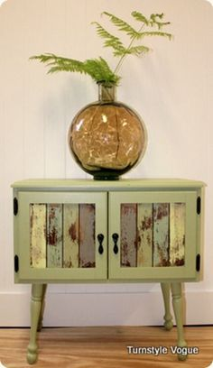 Small green cupboard. Lovely use of multi colours on the doors, and that rustic look.