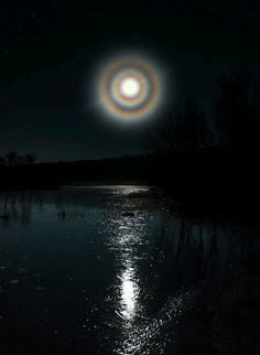 A rare triple halo surrounds the full moon.