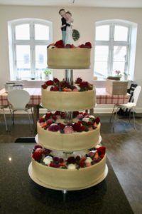 Denne bryllupskage består af en luftig vaniljebund, en frisk hindbær/rabarber mousse med skyr, en sprød nøddemarengs bund og en cremet hvid chokolademousse