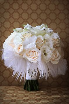 An old Hollywood bouquet of creamy ivory roses accented with airy white feathers.
