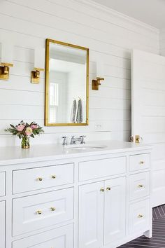Stunning white bathroom with gold accents boasts a Restoration Hardware Rivet Mirror hung from a white shiplap wall between antique brass sconces. #bathroomideas