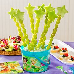 Tinker Bell Theme - Fairies love fruits, veggies and other goodies from nature. Use star cookie cutters to cut your birthday girl's favorite fruit into star shapes. Make a fruit kabob with grapes topped with your star-shaped fruit. Serve these tasty wands in a Tinker Bell container and let your guests grab one whenever they need a bite.