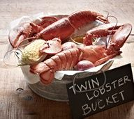 The Maine Event - Twin Lobster Bucket: Two whole split lobsters, corn and potatoes boiled in a garlic bath and topped with Old Bay® Seasoning.   #JoesCrabShack #JoesMaineEvent #TwinLobsterBucket #Lobster #Bucket