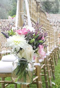 A mason jar arrangement of white Dahlia, pink Lisianthus, cream Rose, and purple Limonium hanging from white voile ribbon as a sweet pew end decoration.