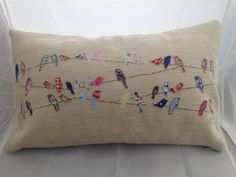 cushion / pillow in cream  with shabby style appliqued little birds sat on a wire.