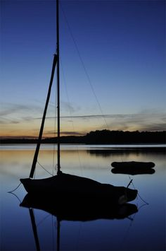 Silhouette of a sailboat on Lake St. Helen at St. Helen, Michigan