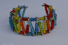 Rainbow Safety Pin Bracelet. This is a nice idea for an alternative design for a safety pin bracelet.