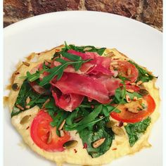 Good morning everyone!  I'm kick starting my day with my favourite flavour combo. A tomato & basil omelette topped with fresh rocket crispy parma ham and a sprinkling of chilli spiced seeds  I used two whole eggs  60g @musclefooduk liquid egg whites for my omelette and add fresh basil leaves sliced tomato pink salt & pepper and cooked it in @lucybeecoconut oil. To make the crispy Parma ham I simply tore up two slices and cooked it in a little more coconut oil until it was nice and crispy (a…