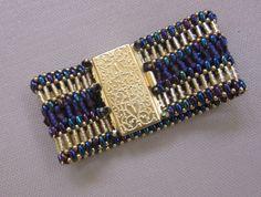 Purple iris handmade signature cuff bracelet.  Golden twisted bugle beads, Swarovski crystals.  Red carpet ready cuff.  Filigree closure. by TreasuresFromDee on Etsy https://www.etsy.com/listing/456189962/purple-iris-handmade-signature-cuff