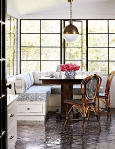 Breakfast nook with a built bench seating, a pendant light and large windows with black frames