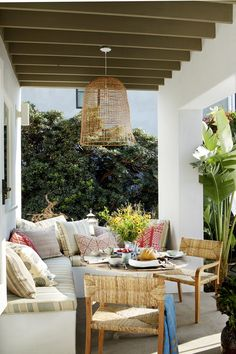 At interior designer Kathryn M. Ireland's compound in Santa Monica, the built-in stucco sectional in the outdoor lounge is topped with cushions in a custom Kathryn M. Ireland outdoor fabric. The table is from her French Finds collection, and the chairs are by Consort.