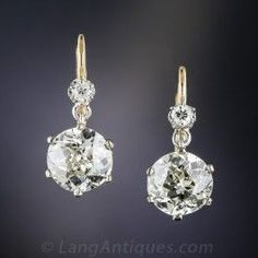 A beautifully matched pair of European-cut diamonds, weighing 1.88 and 1.77 carats respectively (3.85 carats total), swing and sway and seriously sparkle below tiny round stones in these rare, radiant and resplendent original vintage ear drops hand fabricated in two-tone 18K yellow and 14K white gold - circa 1910-1920.