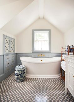 A white pedestal bathtub sits on black and white lattice floor tiles beside a blue and white chinoiserie drum stool table and beneath a gray framed window located above an antique brass wall mount tub filler.