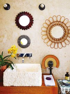 Vintage French mirrors and a Colombian fan enliven the guest bath of interiors stylist Carlos Mota's Dominican Republic retreat; the wall tile and sink are both coral stone, and the sink fittings are by Axor.