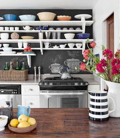 Create a sense of space with open shelving. In this kitchen, simple white planks and custom brackets set against a playful chalkboard-painted wall. RELATED: 7 Easy Kitchen Makeover Ideas Under $50   - CountryLiving.com
