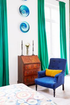 A blue armchair and wood desk in a while room with green curtains
