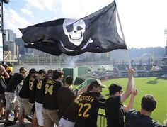 Pittsburgh Pirates fans wave a Jolly Roger flag as they stand in the left field rotunda before Game 3 of a National League division baseball series between the Pirates and St. Louis Cardinals on Sunday, Oct. 6, 2013, in Pittsburgh .(AP Photo/Don Wright)