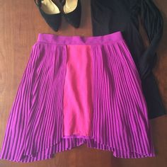 "Unique Millau magenta and purple pleated skirt Fabulous Millau skirt featuring a pink panel down the front with a straight hem an angled down from there on each side of mini pleated purple skirting. Skirt zips closed in back via a hidden zipper. 100% polyester and measures about 30"" at the longest point. Minimal wear--great condition. Millau Skirts"