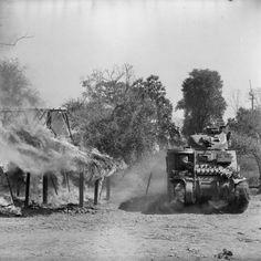 Char M3 Lee passant un bâtiment en feu dans un village birman au sud de Mandalay, le 20 mars 1945.