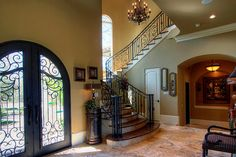 Open entry, spiral staircase with arched windows staggered on up (light/sense of outdoors) wrought iron double doors and on staircase