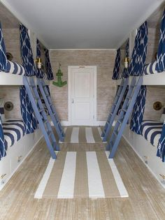 Blue and gray bunk room features built-in bunk beds dressed in white and blue bedding finished with blue knotted rope print curtains illuminated by brass cage sconces lined with blue ladders facing each other across from taupe striped jute rugs.