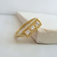 Vintage-inspired, this ring features three square cut white topaz with milgrain edging that gives it a delicate feel. Reminiscent of a more glamorous, art deco time, this ring has a matte gold finishe Charm Jewelry, Gold Jewelry, Jewelry Rings, Jewelery, Fine Jewelry, Sparkly Jewelry, Jewelry Box, 14k Gold Ring, Topaz Ring