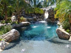 Lagoon backyard pool with beach entry, man-made boulders, rocks and ...