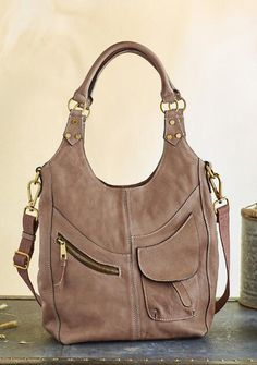 This leather hobo bag features chic lines and unique pocketing for a stunning silhouette.